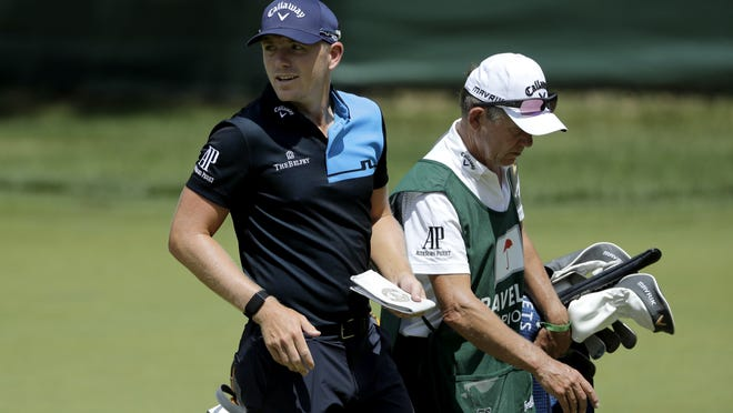 Matt Wallace, left, of England, walks with his caddie David McNeilly to the fourth tee box during the second round of the Travelers Championship golf tournament at TPC River Highlands on Friday in Cromwell. Wallace is playing the second round by himself after two other golfers in his group, Denny McCarthy and Bud Cauley, withdrew from the tournament. Tuesday.
