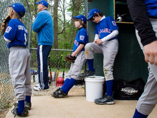 Rangers players wait with a coach in the dugout during a game at Eagle Park on the first day of 2010 South Hanover Little League.