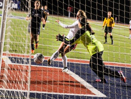 Kat Whitman drives the ball past #16 Danielle Heim
