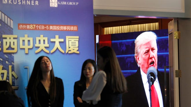 A projector screen shows a footage of U.S. President Donald Trump as workers wait for investors at a reception desk during an event promoting EB-5 investment in a Kushner Companies development at a hotel in Shanghai, China, Sunday, May 7, 2017. The sister of President Trump's son-in-law, Jared Kushner, has been courting Chinese investors using a much-criticized federal visa program that provides a path toward obtaining green cards.