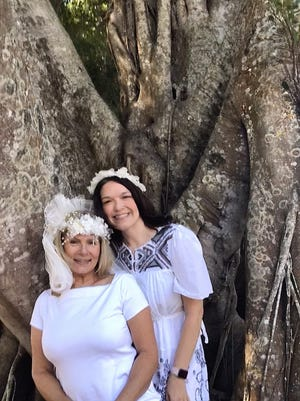 """Brides Karen Cooper, left, and Dana Foglesong pose for a wedding photo in front of their """"groom,"""" an ancient ficus tree they've vowed to cherish and protect."""