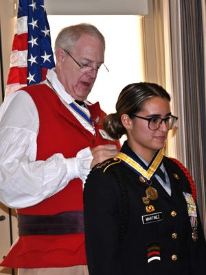 Golden Gate High School JROTC Capt. Thais Martinez, 17, receives an outstanding citizen medal from Michael Garey, president of the Sons of the American Revolution Naples chapter on Feb. 9, 2017. Martinez, along with six other JROTC cadets in Collier County, were honored by the chapter during a luncheon.