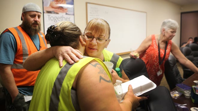 Tonya Bolton, whose two sons are in recovery from heroin, hugs a coworker after a group meeting at Dorman Products in Warsaw, Kentucky.