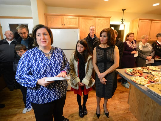 Blanca Villers, right, listens as family advocate Monica Moreau, left, blesses the home and presents a bible in Blanca's new Habitat for Humanity home during Friday's dedication ceremony.