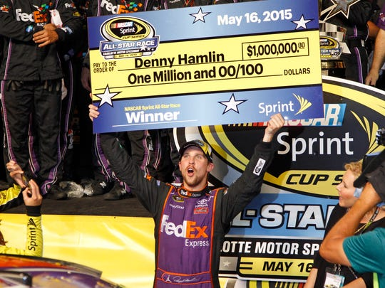 Denny Hamlin holds the mock check after winning the NASCAR Sprint All-Star auto race Saturday at Charlotte Motor Speedway in Concord, N.C.