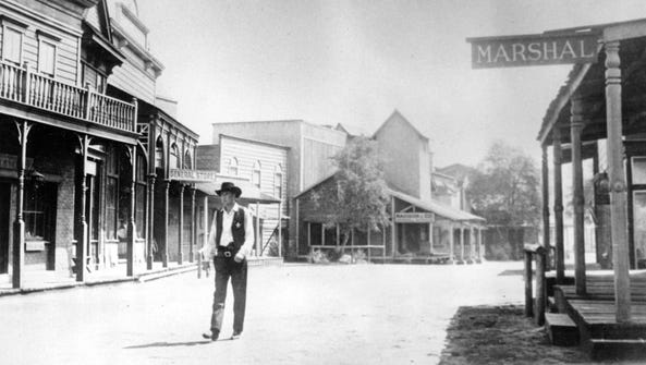 Gary Cooper, portraying a sheriff, walks down the deserted