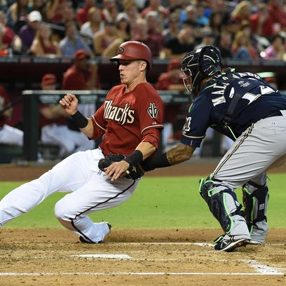 Jake Lamb of the Arizona Diamondbacks is tagged out at home plate by Martin Maldonado of the Milwaukee Brewers during the second inning at Chase Field in Phoenix, Arizona.