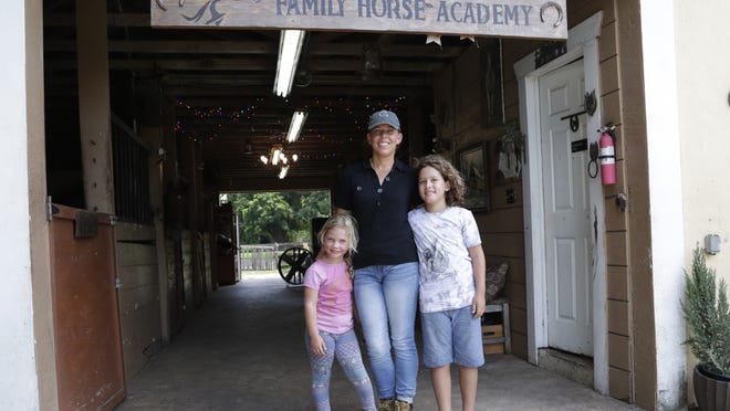 Timea Hunter poses for a photograph with her children Lena, left, and Liam, right, at the Family Horse Academy, where she is hoping to organize education for a group of children during the coronavirus pandemic,, July 31 in Southwest Ranches, Fla.