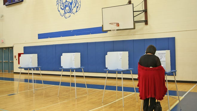 A voter casts her ballott at Westlane Middle School polling site, Tuesday, November 3, 2015.