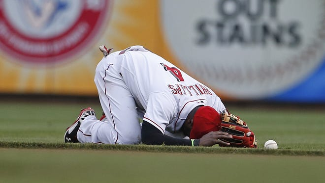 Cincinnati Reds second baseman Brandon Phillips (4) holds his head as he bobbled a ball after making a diving stop of a sharp hit off the bat of Toronto Blue Jays third baseman Brett Lawrie.