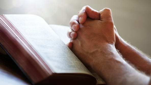 Praying hands on a Holy Bible