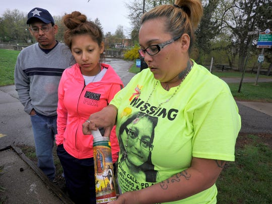 Robert Betancourt, Teresa Betancourt and Sophie Munoz, left to right, ex-husband and daughters of Josephina Betancourt, light candles near the Brenke Fish Ladder in north Lansing Tuesday. Josephina Betancourt has been missing since April 25, and family members have been keeping a vigil ever since.