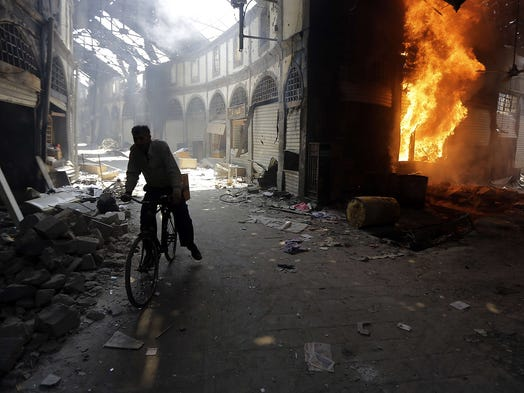 A man rides past a burning shop at the Maskuf market on May 12 in the Old City of Homs, Syria. Residents began returning to the city on May 10 after rebel forces, besieged for nearly two years, left the area under a negotiated evacuation deal with the Syrian government.