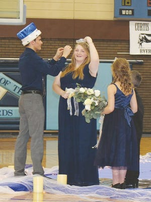 Skyline 2020 Winter Homecoming King Steve Fisher and Queen Kayla Urban work together to secure the crown while attendants Bryleigh Fox and Connor Smiley watch on Friday during the 'Winter Wonderland' festivities.