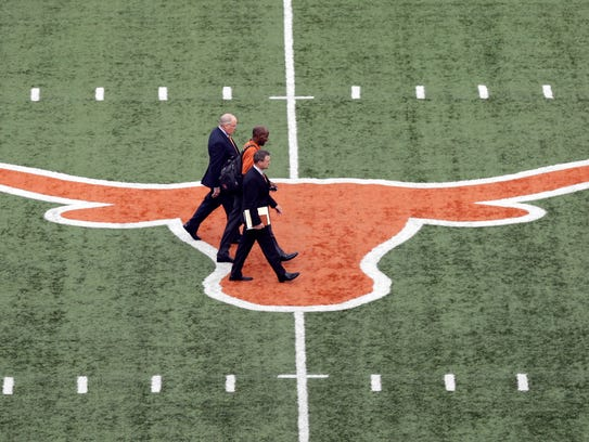 Tom Herman, center, walks across the Texas logo at