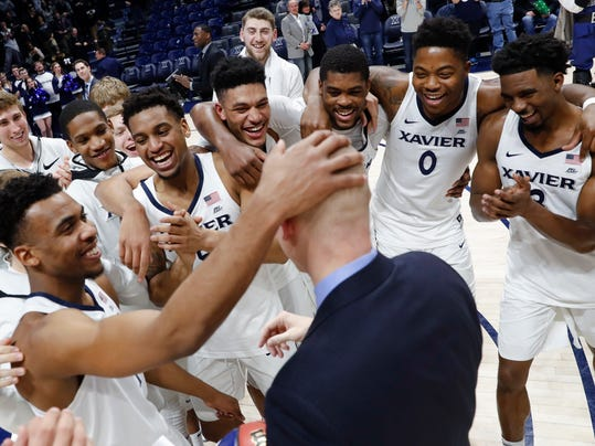 Xavier head coach Chris Mack, center, celebrates with his players after becoming the winningest coach in Xavier's history after an NCAA college basketball game against St. John's, Wednesday, Jan. 17, 2018, in Cincinnati. Xavier won 88-82. (AP Photo/John Minchillo)
