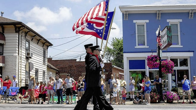 A firefighters colorguard marches during in downtown Westerville during the 2019 Fourth of July parade. There will be no traditional parade this year, but city officials said they are planning a mini 'parade' of city and school district vehicles that will travel through several neighborhoods.