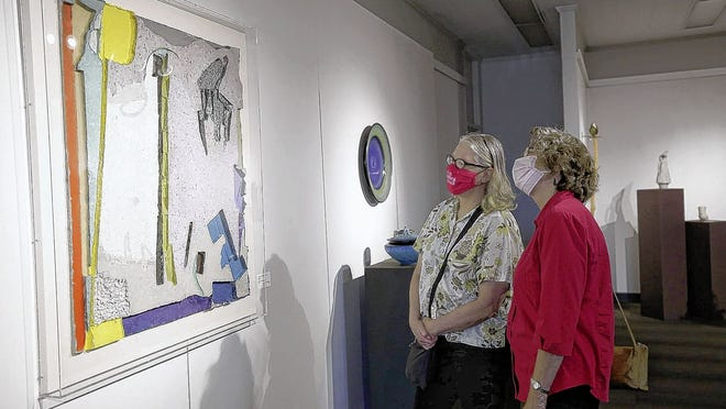 "Connie Pottle and Rachel Alexander, both of Clintonville, examine a piece by Cleveland artist Tom Balbo titled ""From Voids to Regeneration"" on June 25 at the Ohio Craft Museum. The museum, which is north of Grandview Heights and reopened June 16, now requires all visitors to wear masks -- but handmade masks created by local artists are for sale in its gift shop."