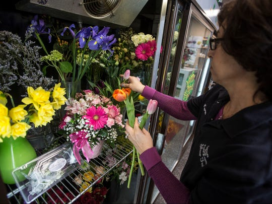 Designer Karen Gambino pulls flowers from the cooler at Silver Tulip Florist in Middletown.