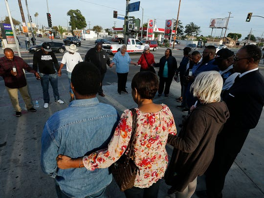 People gather for a prayer circle with South Los Angeles civil rights clergy leaders and members of the community on Monday, April 24, at the intersection of Florence and Normandie in South Los Angeles, to remember all those who lost their lives nearly 25 years ago in the worst race riot in U.S. history.