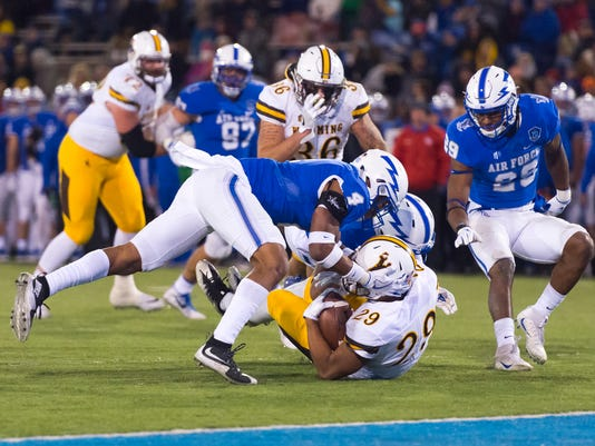 Wyoming running back Kellen Overstreet (29) is brought down by Air Force defensive back James Jones IV (4) in an NCAA college football game at the United States Air Force Academy, Colo., Saturday Nov. 11, 2017. (Dougal Brownlie/The Gazette via AP)