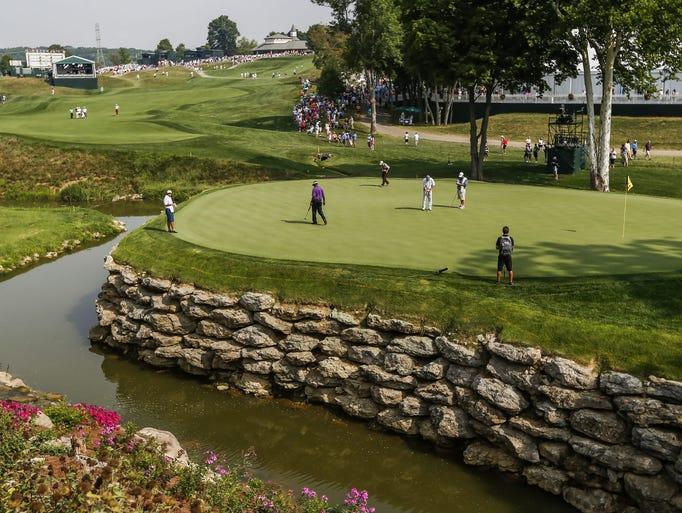 Vijay Singh walks across the thirteenth green as Jason Bohn putts during a practice round at Valhalla Golf Club in Louisville.