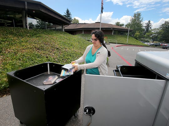Bethany Smith retrieves returned items from the drop box outside the Sylvan Way branch of the Kitsap Regional Library last month. KRL is eliminating late fees, which it views as a barrier to people, especially children, checking out books.