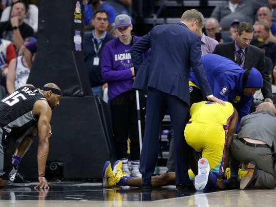 Sacramento Kings forward Vince Carter, left, watches as Golden State Warriors' Patrick McCaw is tended to after Carter's Flagrant-1 foul caused him to land hard on the court during the third quarter of an NBA basketball game, Saturday, March 31, 2018, in Sacramento, Calif. The Warriors won 112-96. (AP Photo/Rich Pedroncelli)