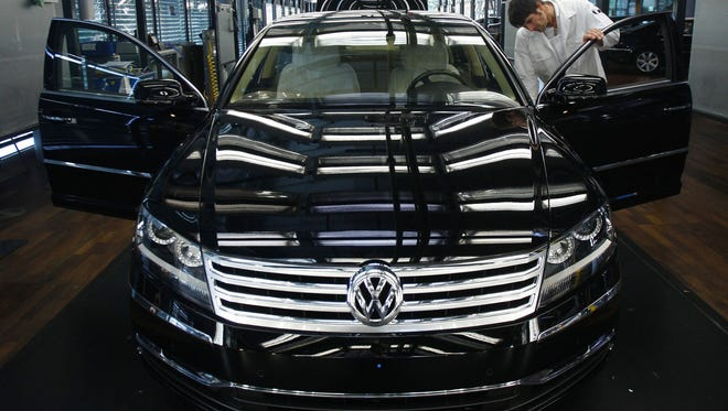 An employee inspects a Volkswagen AG Phaeton in the company's factory in Dresden, Germany. Volkswagen is the world's third-largest automaker, but it has set its sights on becoming the largest by 2018. To some industry experts, that vision seems unrealistic.