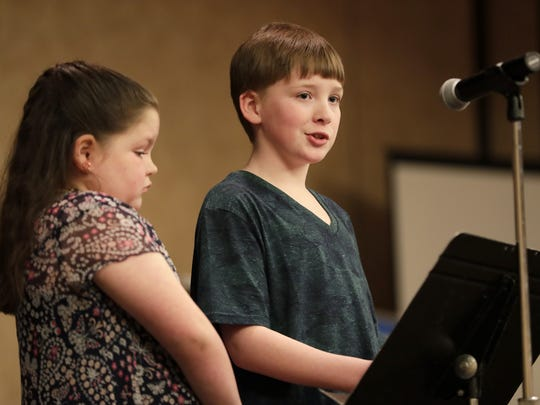 Jonathan Meyer, 12, is joined on stage by his sister, Kensie, 10, on Tuesday as he speaks about his journey through mental illness, part of the Storycatchers portion of USA TODAY NETWORK-Wisconsin's Appleton Kids in Crisis town hall at the Radisson Paper Valley Hotel in Appleton.