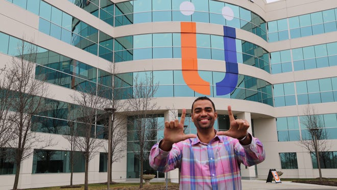 Former Michigan State basketball player stands outside his workplace.