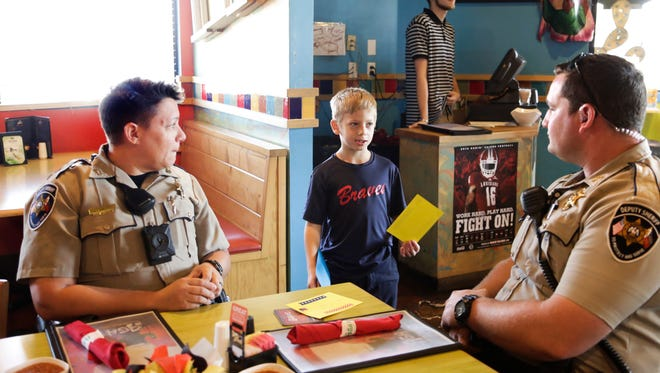 Oliver Perry talks with Lafayette Parish deputies Shelley Landry and Dustin Ardoin during lunch at Agave Sept. 11, 2016. Perry made over $250 at his lemonade stand to feed first responders lunch on September 11.