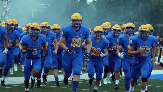IU commit Britt Beery (88) leads the Carmel Greyhounds onto the field.
