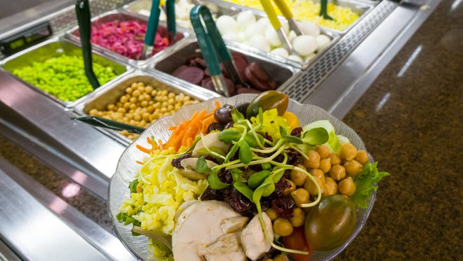 The salad bar at University Hospital includes not only healthier foods but color-coded utensils to indicate healthier options.