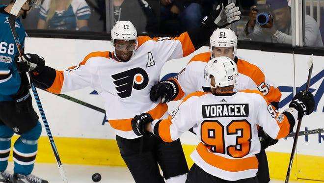 Philadelphia Flyers' Wayne Simmonds celebrates with teammates Valtteri Filppula (51) and Jakub Voracek (93) after scoring a goal against the San Jose Sharks.