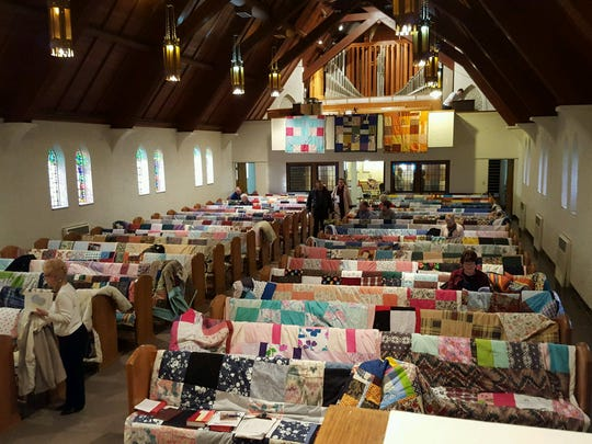 First Lutheran Church pews are covered in quilts ready