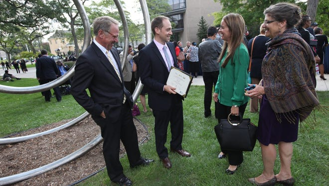 Phil Porter, from left, is with his son, William Porter of Porter One Design in Farmington Hills, who shows off his certificate to his wife, Steffanie Porter, and mom, Valerie Porter, after the Goldman Sachs first graduation of the 10,000 Small Businesses in Detroit at Wayne State University on Thursday. Goldman Sachs Chairman and CEO Lloyd Blankfein, Gov. Rick Snyder, Detroit Mayor Mike Duggan and Warren Buffett were all there.