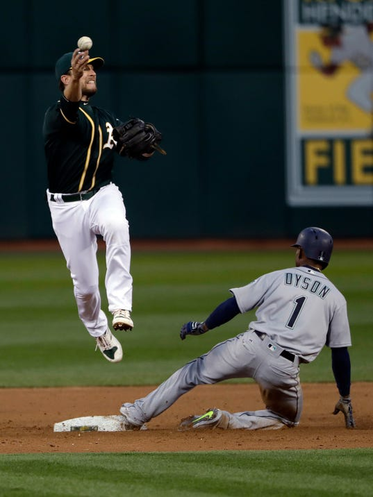 Oakland Athletics second baseman Jed Lowrie, left, throws to first base to complete a double play over Seattle Mariners' Jarrod Dyson (1) on a ground ball from Mitch Haniger during the second inning of a baseball game Thursday, April 20, 2017, in Oakland, Calif. (AP Photo/Marcio Jose Sanchez)