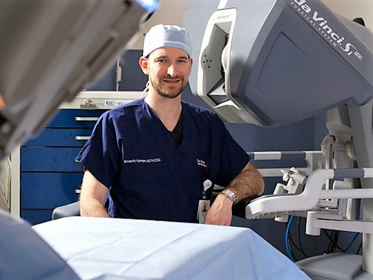 Dr. Richard Farnam, medical director of robotic surgery at Las Palmas Medical Center, poses in front of a da Vinci robotic surgery system.
