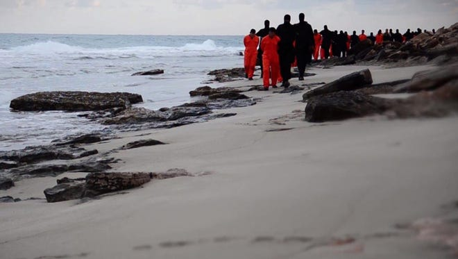 An image grab taken from a video released by the jihadist media arm Al-Hayat Media Centre on February 15, 2015 purportedly shows black-clad Islamic State (IS) group fighters leading handcuffed hostages, said to be Egyptian Coptic Christians, wearing orange jumpsuits before their alleged decapitation on a seashore in the Libyan capital of Tripoli.