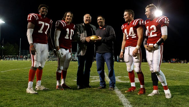 Former Packers great Jerry Kramer presents a golden ball celebrating 50 years of the Super Bowl to his high school alma mater in Sandpoint, Idaho.