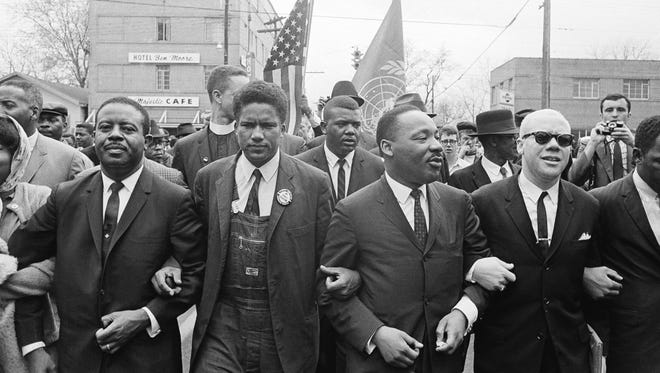 Dr. Martin Luther King, Jr. locks arms with his aides as he leads a march of several thousands to the court house in Montgomery, Alabama, March 17, 1965.  From left: Rev. Ralph Abernathy, James Foreman, King, Jesse Douglas, Sr. and John Lewis.
