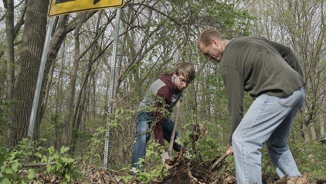 Paul Sabatini and Brian Withun dig out the sidewalk, covered with soil and decomposed leaves, at Helman Park.