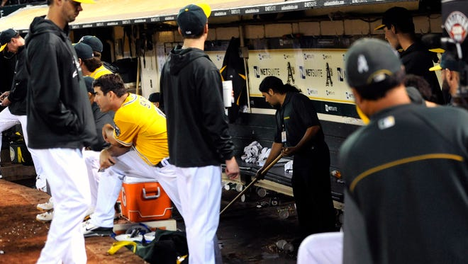 Oakland Athletics cleaning crew mop the deck of the dugout after the bathroom overflowed during the seventh inning.