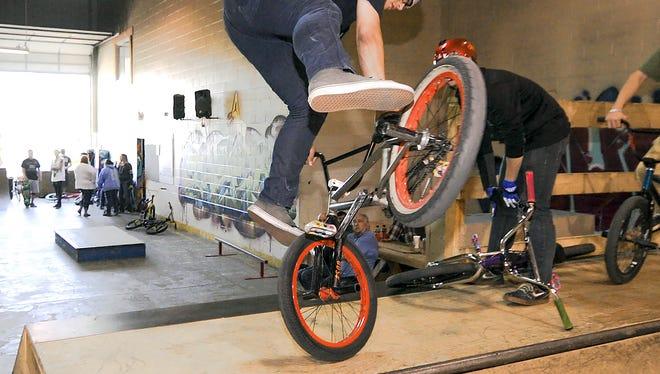 Derek Goff works his bmx bike on the half pipe at Battleground skate park Tuesday night.