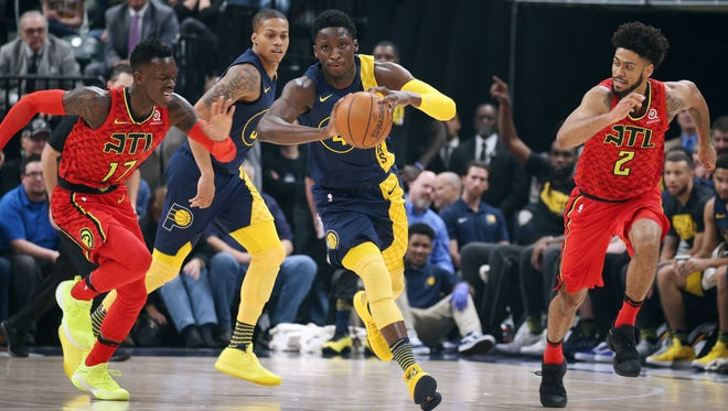 Feb 23, 2018; Indianapolis, IN, USA; Indiana Pacers guard Victor Oladipo (4) leads a fast break against Atlanta Hawks guard Dennis Schroder (17) and guard Tyler Dorsey (2) during the first quarter at Bankers Life Fieldhouse.