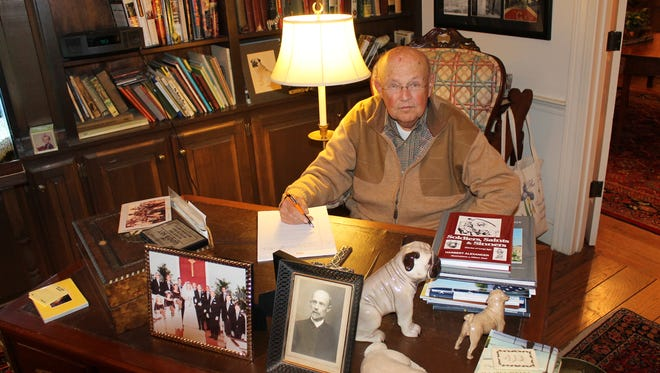 """Author Harbert Alexander of Jackson is shown at his home writing """"place""""-- a desk where he composes using a legal pad and pen.  All of his books have been handwritten."""