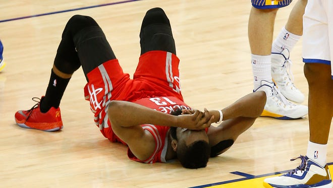 Houston Rockets guard James Harden (13) lays on the ground during the second half of Game 2 of the NBA basketball Western Conference finals against the Golden State Warriors in Oakland, Calif., Thursday, May 21, 2015.