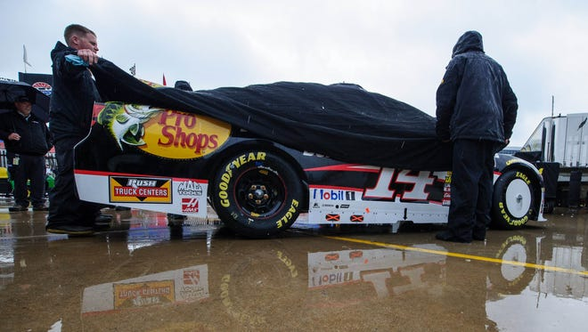 Members of the crew for Sprint Cup Series driver Tony Stewart (14) move their car out of the inspection stall before the Duck Commander 500 at Texas Motor Speedway.