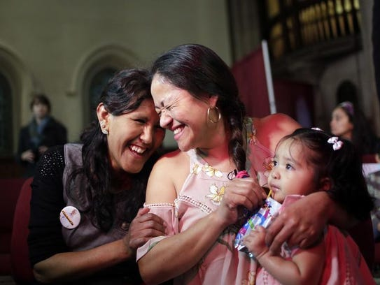 While holding her one-year-old daughter Camila Sanchez,